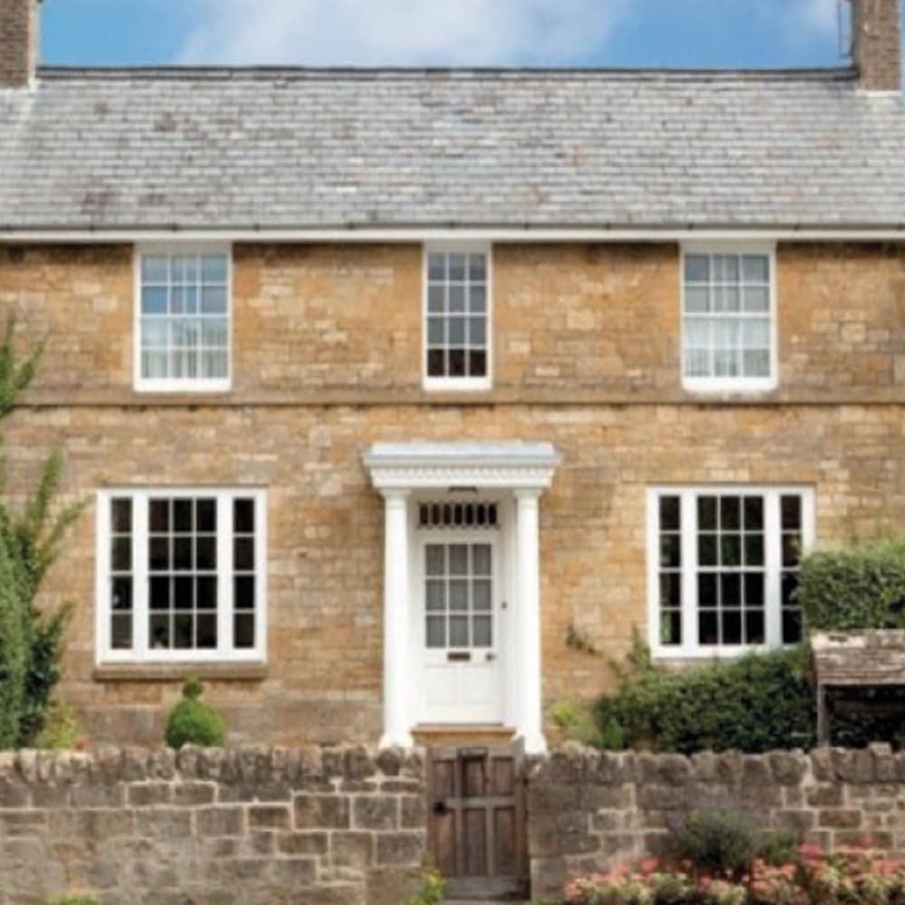 Stone cottage featuring white windows
